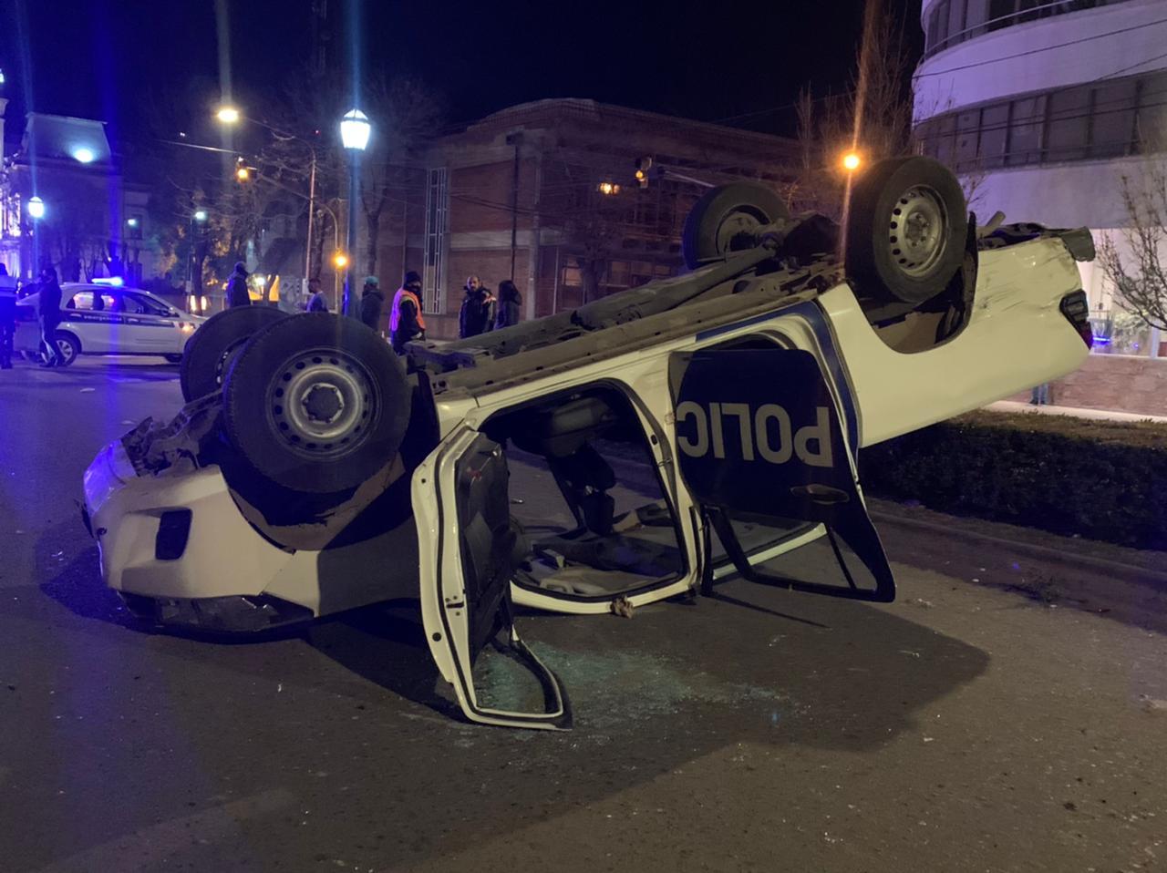 Choque y vuelco frente a la plaza.  (video) Un patrullero quedó con las ruedas hacia arriba